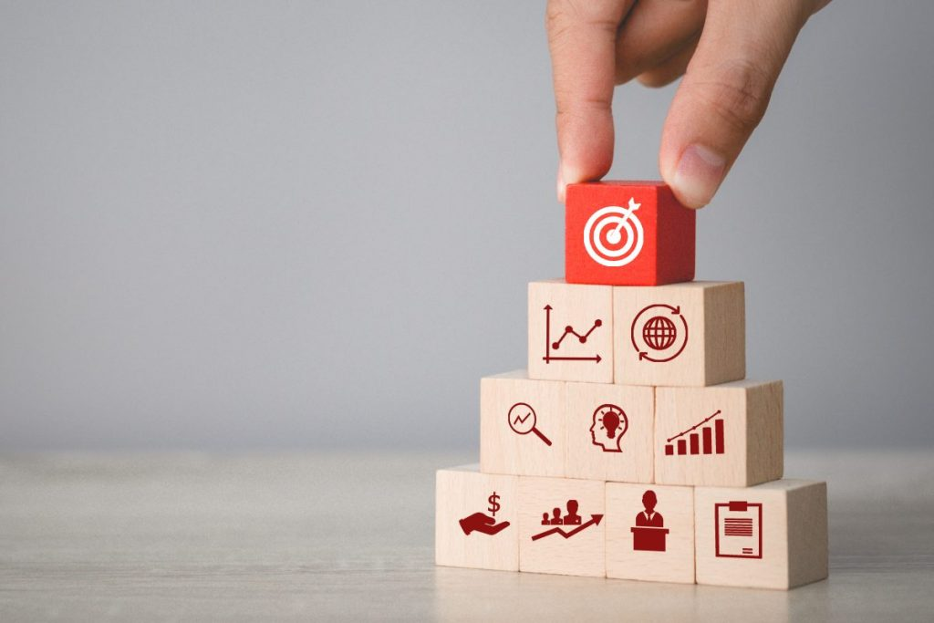 hand-arranging-wood-block-stacking-with-icon-arrow-business-targeting-business-concept